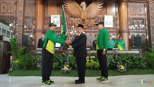 Plt Bupati Tulungagung, Maryoto Birowo (berjas) saat memberikan bendera pada ketua kontingen Tulungagung(foto : Joko Pramono/TulungagungTIMES)