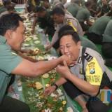Anggota polisi dan TNI saling menyuapi makanan dalam memperingati HUT Bhayangkara. (eko Arif s /JatimTimes)