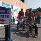 Kanit Regident mendorong kaum difabel menuju ruang foto SIM (foto : Joko Pramono/Jatim Times)