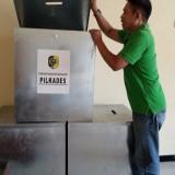 Ketua Panitia Pilkades Desa Bangoan,  Hariyanto memeriksa kotak suara bantuan Pemkab (foto : Joko Pramono/Jatimtimes)