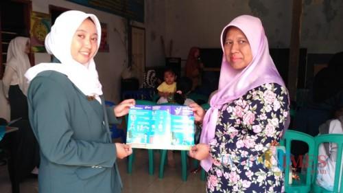 Salah seorang warga dan petugas kesehatan yang menunjukkan pamflet GERMAS saat penyuluhan (Arifina Cahyanti Firdausi/MalangTIMES)