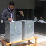 Salah seorang Mahasiswa Unisba Blitar memasukkan surat suara kedalam kotak usai mencoblos.(Foto : Aunur Rofiq/BlitarTIMES)