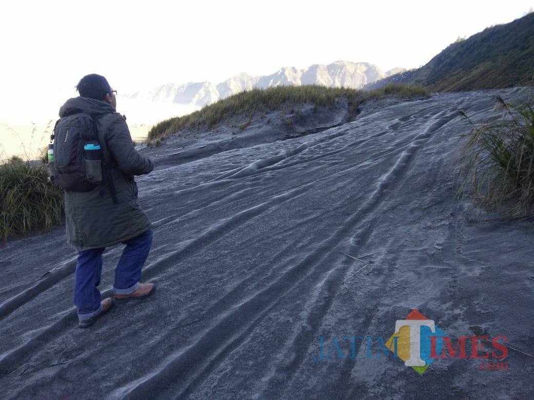Wisatawan tengah berada di lautan pasir Gunung Bromo yang permukaannya diselimuti embun beku seperti salju. (Foto: Dokumen MalangTIMES)
