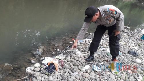 Petugas Polsek Kaliwates saat melakukan olah TKP penemuan mayat bayi yang  terbungkus plastik. (foto : istimewa / Jatim TIMES)