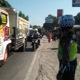 Anggota Satlantas Polres Lumajang yang berusaha mengurai kemacetan di rusa jalan Klakah Wonorejo (Foto : Moch. R. Abdul Fatah / Jatim TIMES)