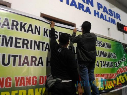 Bupati Lumajang H. Thoriqul Haq ketika memasang banner menandai akhir operasional PT. Mutiara Halim (Foto : Moch. R. Abdul Fatah / Jatim TIMES)