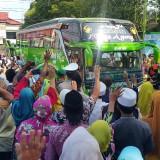 keluarga dan pengantar JCH melambaikan tangannya saat JCH berangkat ke Surabaya (Agus Salam/Jatim TIMES)