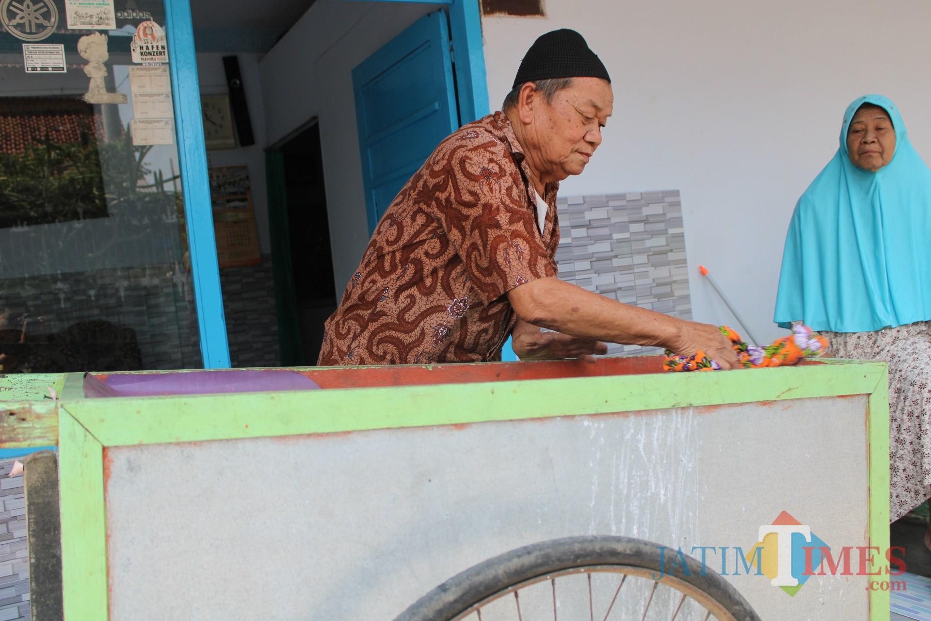 Samsuri saat membersihkan gerobak yang sehari-hari digunakan berjualan bubur. (Foto : Adi Rosul / JombangTIMES)