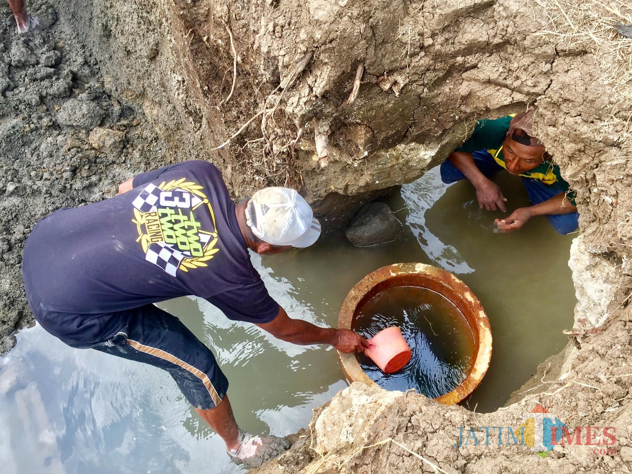 Warga saat menyiduk air sumber air hangat di Sumber Nyi Sindu Dusun Sumbersari, Desa Sumberejo, Kecamatan Batu, Kamis (11/7/2019). (Foto: Irsya Richa/MalangTIMES)