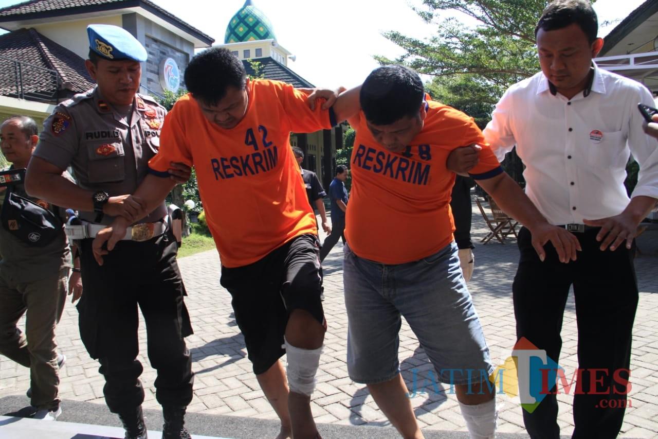 Kedua tersangka saat digelandang petugas di Mapolres Kediri. (eko Arif s /JatimTimes)