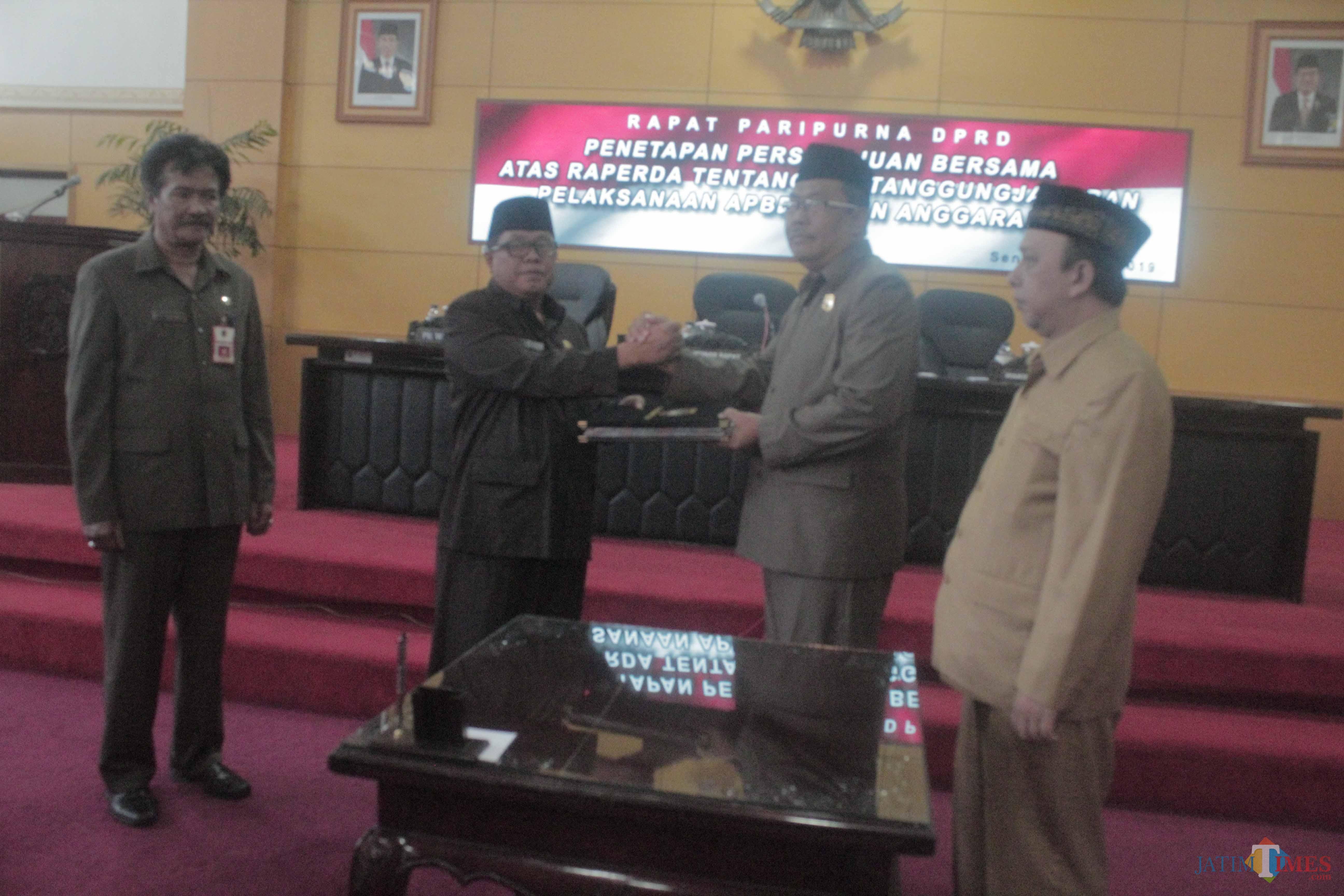 Wakil Ketua DPRD Kota Blitar Slamet menyerahkan dokumen Perda APBD 2018 kepada Plt Wali Kota Blitar Santoso.(Foto : Aunur Rofiq/BlitarTIMES)