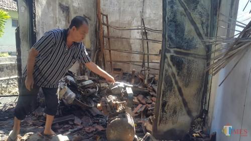 Edi Suprianto tengah membersihkan puing-puing bengkelnya setelah terbakar Selasa dini hari (Agus Salam/JatimTIMES)