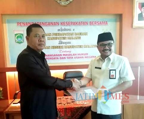 Kepala Bapenda Kabupaten Malang Purnadi (kanan) bersama kajari Kepanjen saat MoU penindakan wajib pajak nakal. (Nana)