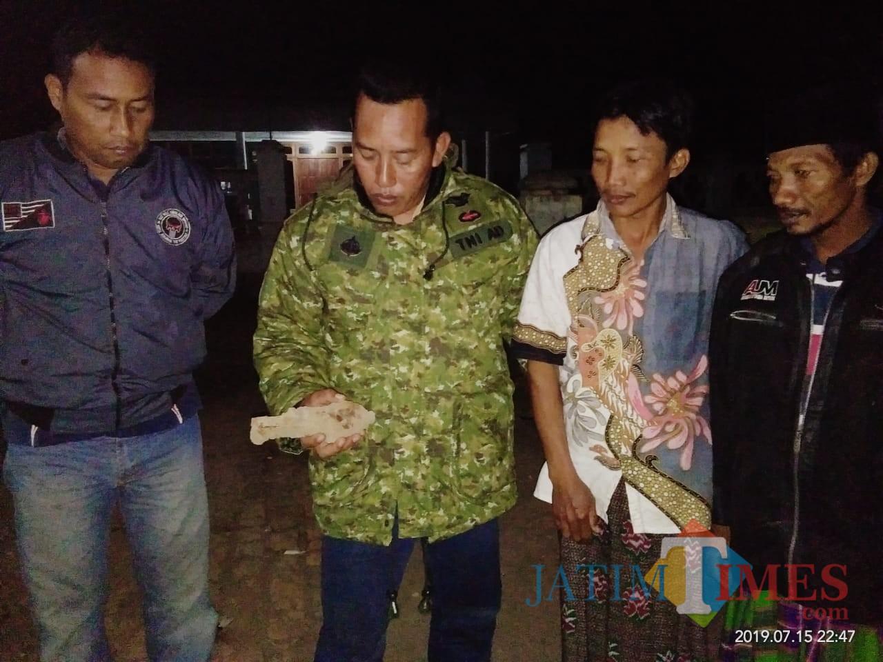 Perangkat desa dan babinsa Serka Mustain saat menunjukkan proyektil besar mirip bom dari Dusun Bulurejo. (foto : Moh. Ali Makrus / Jatim TIMES)