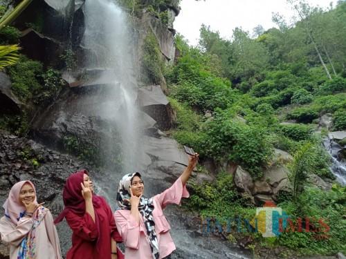 Pengunjung tengah berfoto di wisata alam Coban Putri di Kota Batu. (Foto: Nurlayla Ratri/MalangTIMES)