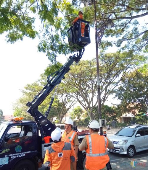 Petugas bidang PJU saat melakukan perawatan PJU di kawasan Jalan Simpang Balapan.(Anggara Sudiongko/MalangTIMES)