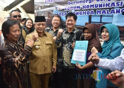 Plt Bupati Malang Sanusi (berpeci hitam) bersama Forum Komunikasi Warga Tionghoa Malang Raya dalam program bedah rumah di wilayah Pagelaran. (Nana)