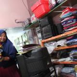 Suminten, penerima PKH tampak sibuk mengurus usaha laundry yang dirintis dari bansos PKH. (Foto : Adi Rosul / JombangTIMES)