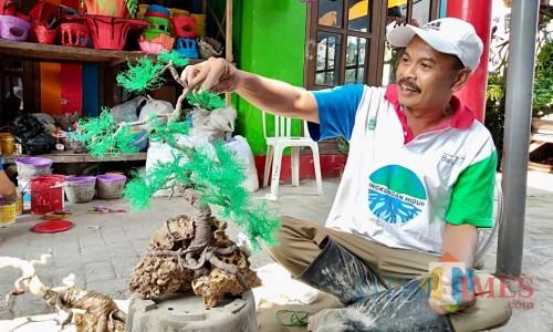 Eko saat membuat replikas bonsai di rumahnya Desa Torongrejo, Kecamatan Junrejo. (Foto: Irsya Richa/MalangTIMES)