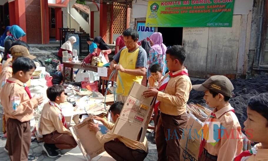 Para wali murid dan murid sedang mengemas sampah belas di halaman MI Darul Ulum Batu.