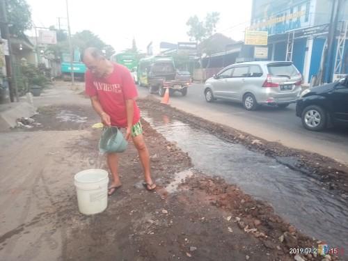 Warga yang harus mengambil air di galian untuk pelebaran jalan yang tergenang bocoran air PDAM (Anggara Sudiongko/MalangTIMES)