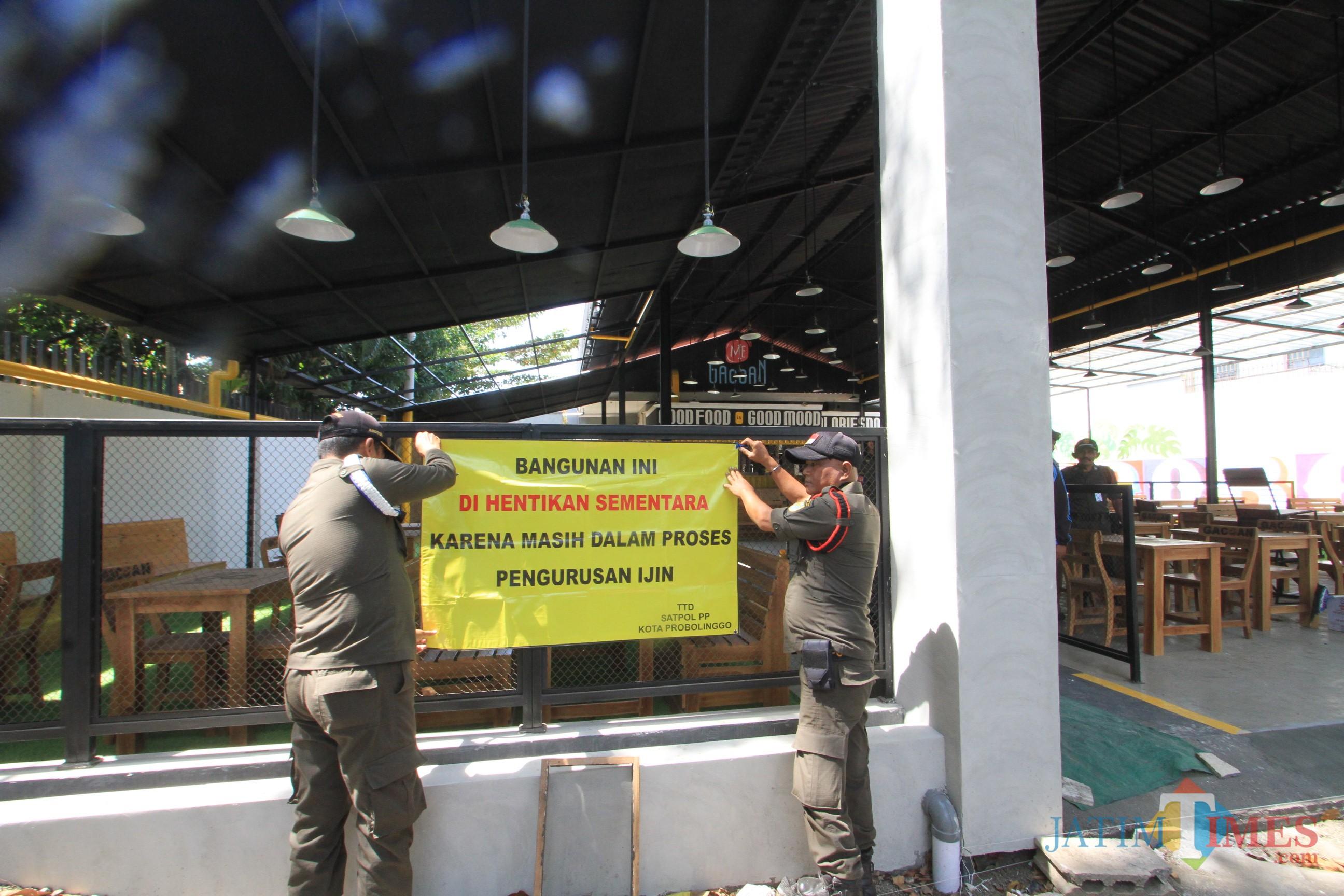 Petugas Satpol PP tengah memasang spandulkk penutupan warung mie di jalan Suroyo, Kota Probolinggo (Agus Salam/Jatim TIMES)