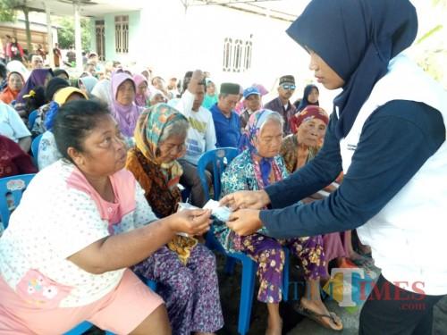 Salah seorang panitia penyelenggara baksos BMH Malang menyerahkan bantuan berupa uang kepada salah satu warga Dusun Licin, Desa Lebakharjo Kabupaten Malang, Sabtu (20/7/2019) lalu (Foto : Igoy/MalangTIMES).
