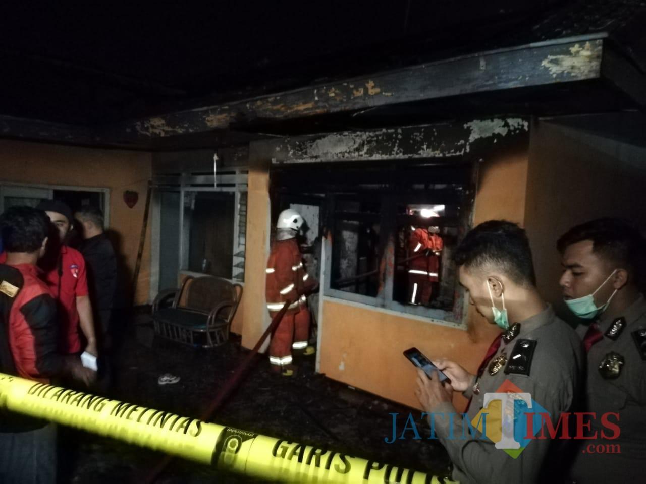 Tim pemadam kebakaran saat memadamkan kebakaran diJalan Hasanuddin No 37 RT 2 RW 5 Desa Junrejo, Kecamatan Junrejo,malam ini Selasa (23/7/2019).