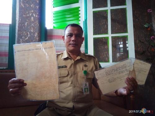 Kepala UPT PPU, Takroni Akbar, saat menunjukkan arsip pendataan buku zaman Belanda di TPU Sukun maupun kwitansi pembayaran pajak makam (Anggara Sudiongko/MalangTIMES)