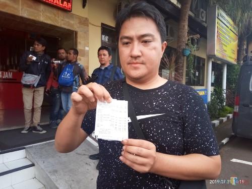 Suami korban yang menunjukan struk palsu yang dibuat oknum penipu online pesan grab food (Anggara Sudiongko/MalangTIMES)