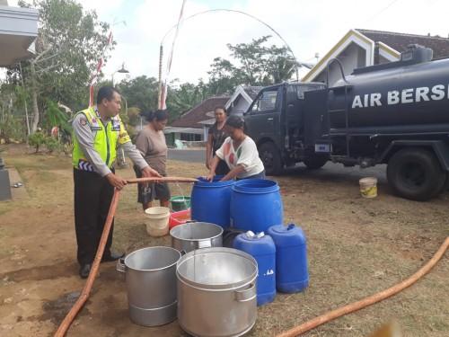 Petugas saat membagikan air bersih kepada warga yang terdampak kekeringan. (Foto : Humas Polres Malang for MalangTIMES)