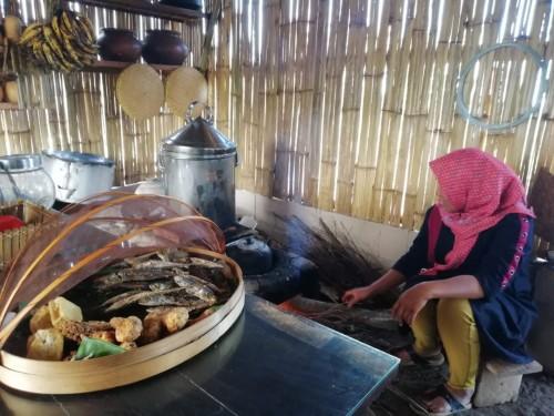 Suhartini saat membuat bara api di Kafe Ubi. (Foto: Irsya Richa/MalangTIMES)