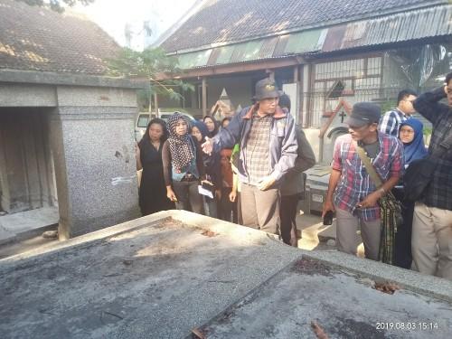 Tim Ahli  Cagar Budaya Kota Malang saat melihat salah satu makam di TPU Nasrani Sukun (Anggara Sudiongko/MalangTimes)