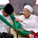 Presiden Republik Indonesia Joko Widodo saat dikalungkan sorban�Kiai Maimun Zubair.