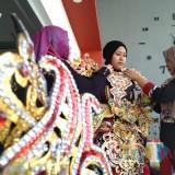salah satu penyewa sedang memasang kostum (foto : Joko Pramono/JatimTIMES)
