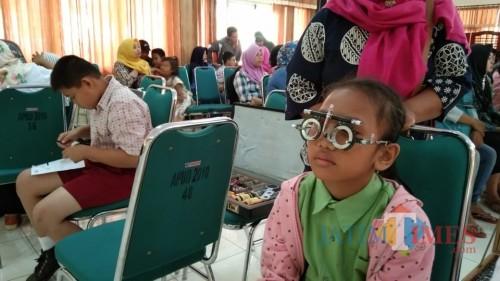pelajar penerima kacamata greatis saat diperiksa penglihatanya (foto : Joko Pramono/ Jatim Times)