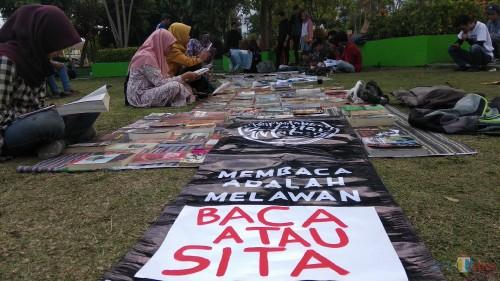 Para pengunjung Taman Singha Merjosari, Kota Malang tengah membaca buku dalam kegiatan Lapak Baca Solidaritas Malang. (Foto: Nurlayla Ratri/MalangTIMES)