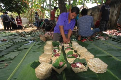 Salah satu panitia kurban membungkus daging kurban dengan besek yang dilapisi daun pisang (Agus Salam/Jatim TIMES)