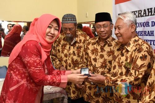 Ketua PMI Kota Kediri Lilik Muhibbah saat menyerahkan cincin emas kepada para pendonor.(eko Arif s/JatimTimes)