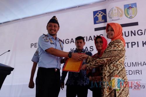 Bupati Kediri Hj Haryanti Sutrisno menyerahkan IMB kepada Kepala Imigrasi Kediri. (eko Arif s /JatimTimes)
