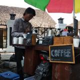 Achmad Yusuf saat meracik kopi yang dipesan pembeli. (eko Arif s /JatimTimes)