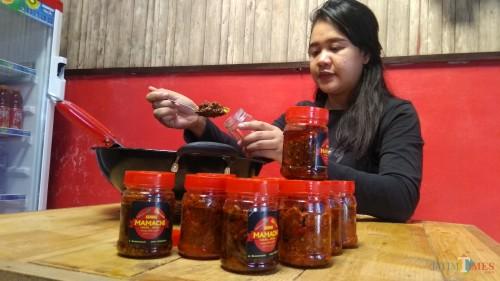 Owner Sambal Mamacih tengah mengemas sambal kemasan. (Foto: Nurlayla Ratri/MalangTIMES)