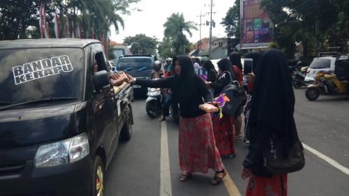 Pelaku UMKM di Banyuwangi membagikan produknya kepada pengguna jalan.