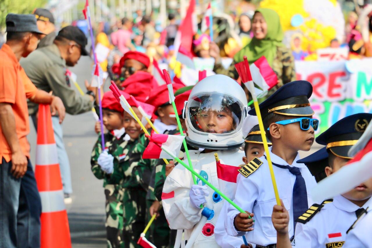 Deretan siswa yang menggunakan pakaian astronot, TNI, dan pilot di jalan protokol Panglima Sudirman, Kecamatan Batu, Kamis (15/8/2019).