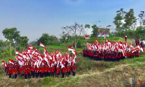 Para pelajar yang mengibarkn bendera didi atas kali Lanang, Desa Pandanrejo, Kecamatan Bumiaji, Jumat (16/8/2019). (Foto: Irsya Richa/MalangTIMES)