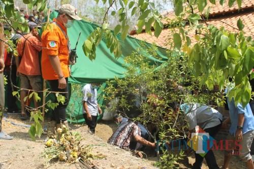 Petugas dibantu warga membongkar dan memindahkan makam Suryat Suyono setelah didemo warga sekitar. ( foto : Joko Pramono/Jatim Times)