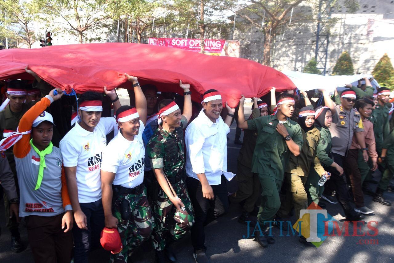 Walikota Kediri Abdullah Abu Bakar bersama Forkopimda dan ribuan pelajar di Kota Kediri mengarak bendera berukuran raksasa. (eko Arif s /JatimTimes)