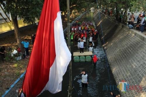 Proses pengibaran bendera merah putih pada momen upacara Proklamasi Kemerdekaan RI yang dilakukan oleh aktivis lingkungan di Sungai Avoor Pandan Jombang. (Foto : Adi Rosul / JombangTIMES)
