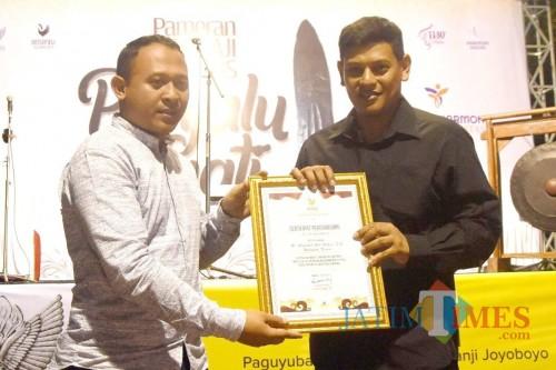 Wasekjen Senapati Nusantara Nurjianto (kiri) menyerahkan penghargaan kepada Wali Kota Kediri Abdullah Abu Bakar (kanan). (Foto: Bambang Setioko/JatimTIMES)