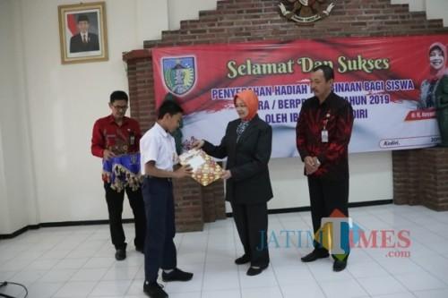 Bupati Kediri Hj Haryanti Sutrisno menyerahkan penghargaan kepada siswa berprestasi.(eko Arif s /JatimTimes)